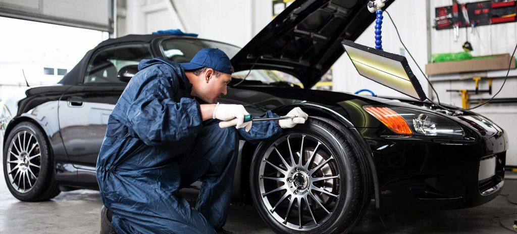 Car Serviced by Mechanic in Auto Body Shop